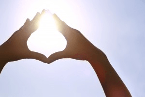Image of hands encompassing sun in heart shape being emblematic for Hypnotherapy Treatments